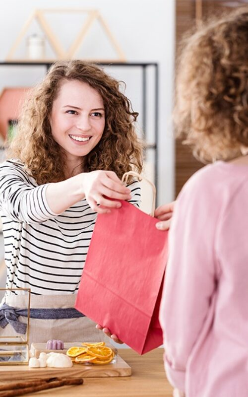 Saleswoman handing out a bag in her store using badgy to create her loyalty cards